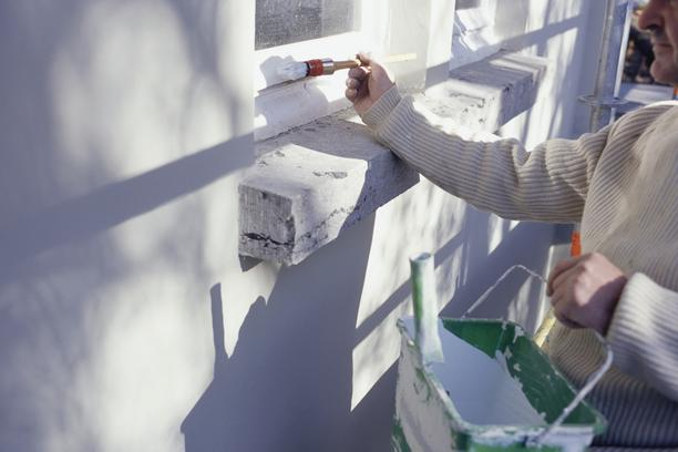 Man painting window frames white